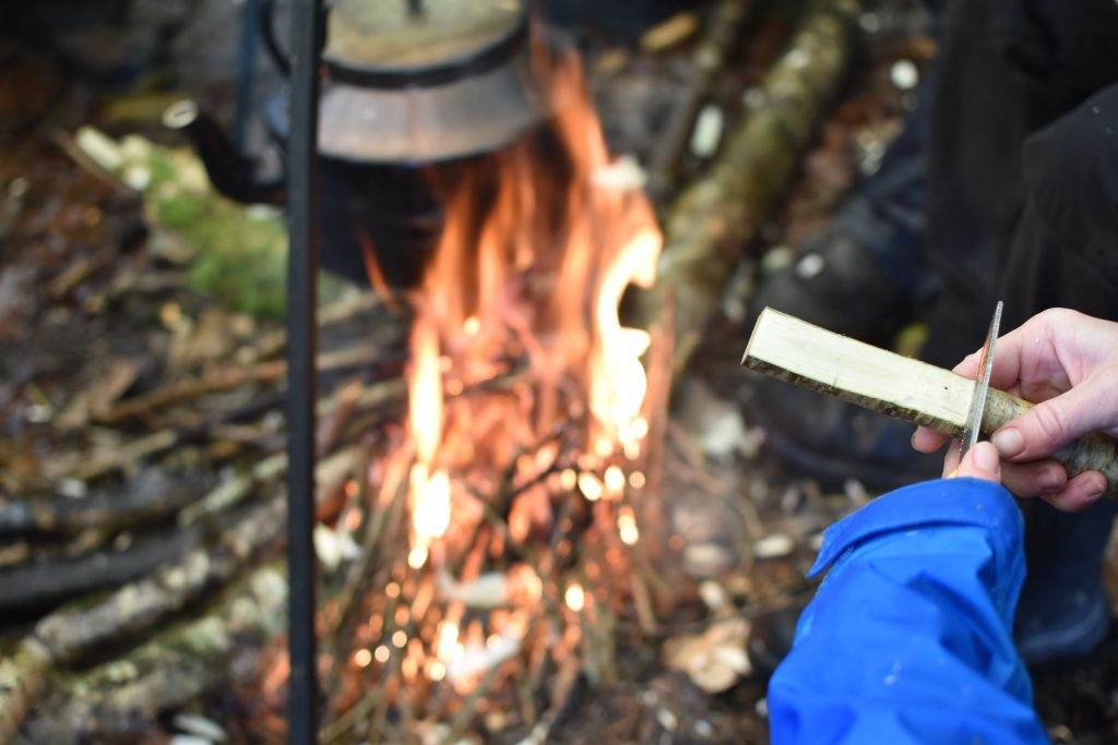 Whittling a butter knife by the fire